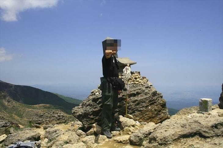 登山で山頂でポーズを決める鈴木